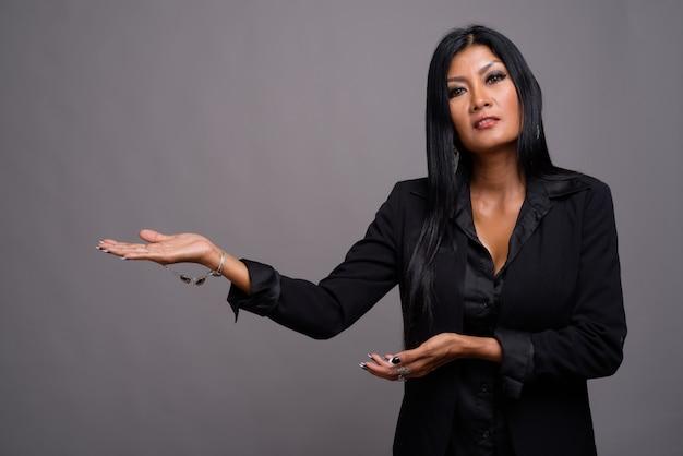 Coppia bella asiatica imprenditrice contro uno sfondo grigio