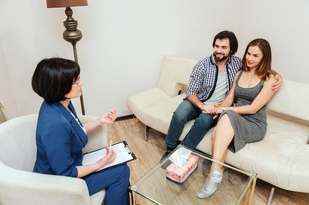 Coppia bella e felice è seduta insieme e si abbracciano. stanno guardando il dottore e stanno sorridendo. il terapista sta parlando con loro.