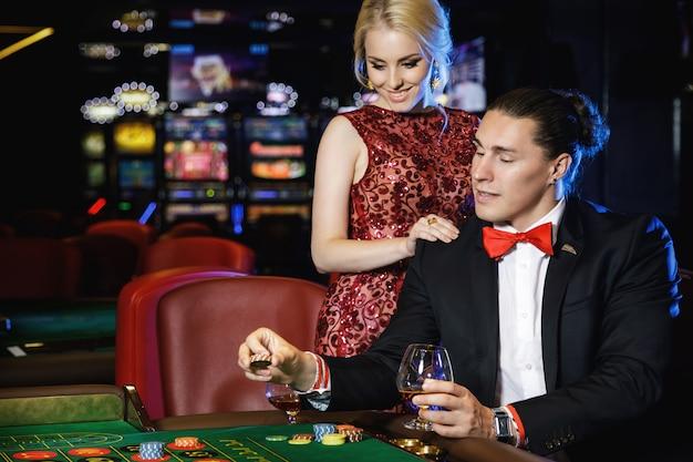 Coppia bella e ricca che gioca alla roulette nel casinò