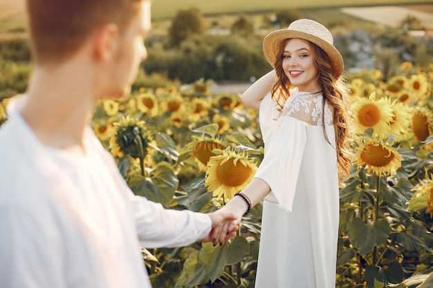 Coppia bella ed elegante in un campo con girasoli