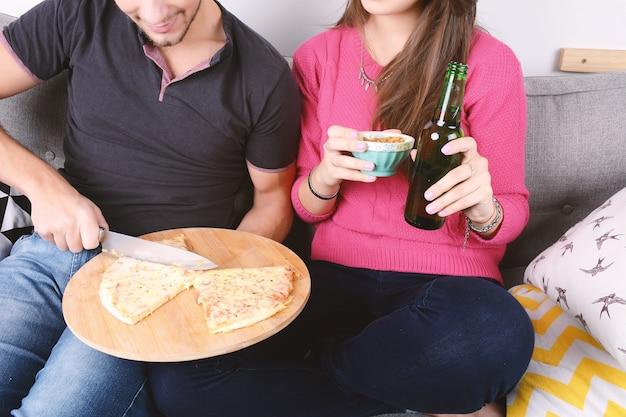 Coppia bere birra e mangiare la pizza.