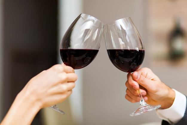 Coppia brindando con bicchieri da vino