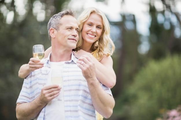 Coppia brindando con champagne fuori
