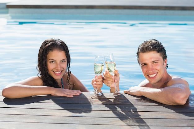 Coppia brindando con champagne in piscina