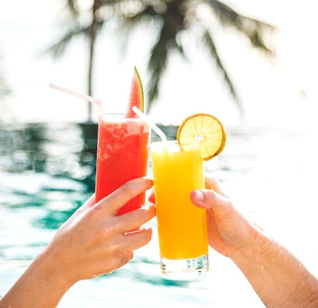 Coppia brindando con cocktail a bordo piscina