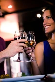 Coppia brindando con un bicchiere di vino in un bar