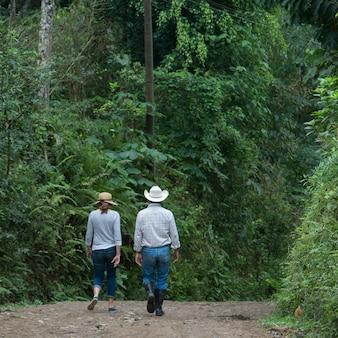 Coppia camminando su una strada nella foresta, finca el cisne, honduras