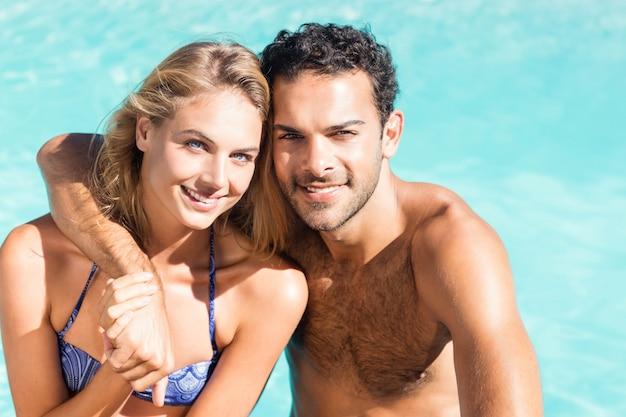 Coppia carina abbracciarsi a bordo piscina