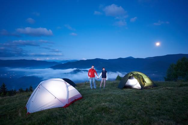 Coppia carina è in piedi vicino al campeggio tenendosi per mano sullo sfondo del paesaggio montano del mattino. una splendida vista sulle montagne nella foschia mattutina, il cielo blu all'alba e la luna luminosa