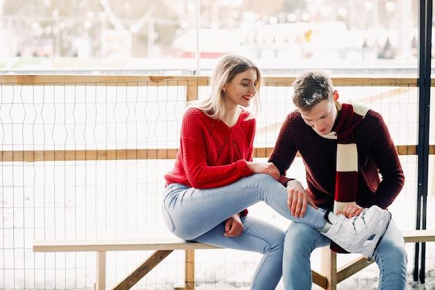 Coppia carina in maglioni rossi si aiutano a pattinare