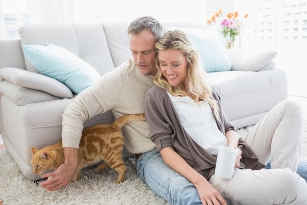 Coppia carina seduto con caffè e accarezzare il loro gatto