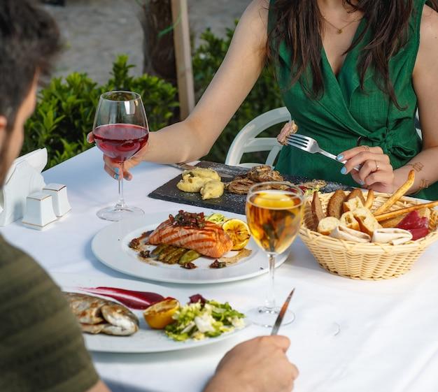 Coppia cenando con filetto di salmone affumicato, pesce grigliato, bistecca di agnello e vino