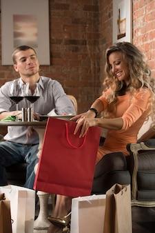 Coppia cenare insieme in un ristorante al coperto dopo lo shopping