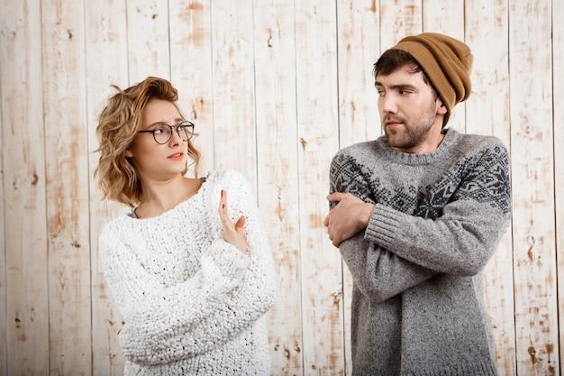 Coppia cerca a vicenda sul muro di legno rifiuti di ragazza.