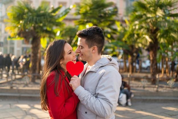 Coppia che copre il loro bacio con un cuore