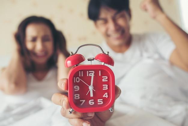 Coppia che ha difficoltà a alzarsi presto la mattina sul letto