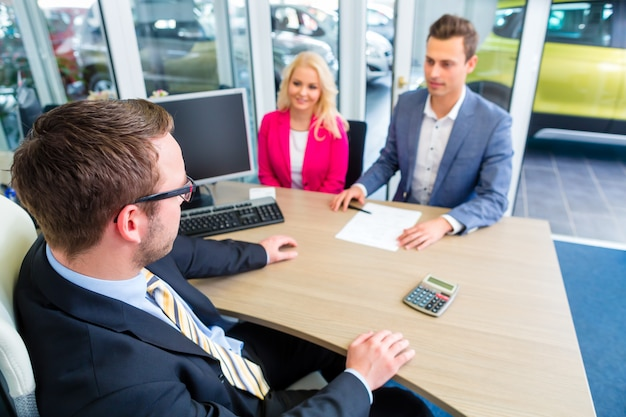 Coppia che negozia i contatti di vendita per l'auto
