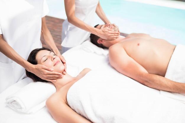 Coppia che riceve un massaggio al viso da massaggiatore in una spa