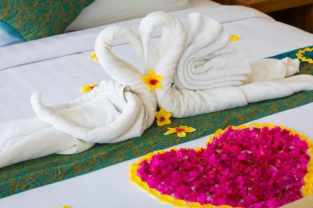 Coppia cigno messo sul letto luna di miele con petali di rose per gli amanti della luna di miele