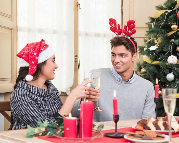 Coppia clanging bicchieri di champagne al tavolo festivo