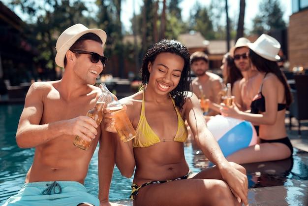 Coppia con bevande alcoliche a bordo piscina