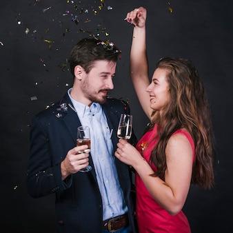 Coppia con bicchieri di champagne sotto lustrini