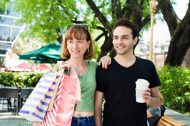 Coppia con borse della spesa camminando per le strade.
