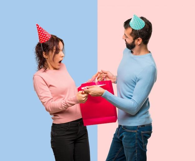 Coppia con cappelli di compleanno e con borse della spesa su sfondo rosa e blu