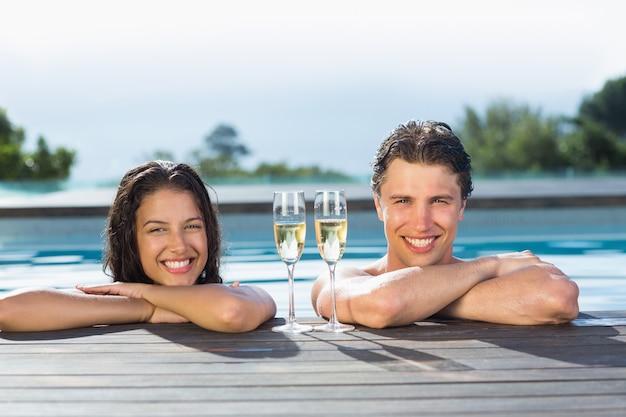 Coppia con champagne flauti in piscina