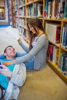 Coppia con libri presso il corridoio della biblioteca