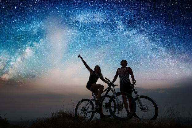 Coppia con mountain bike sotto il cielo stellato di notte