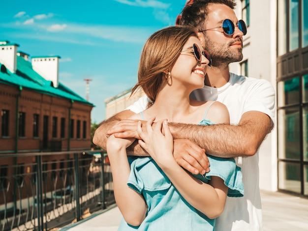 Coppia con occhiali da sole in posa in strada