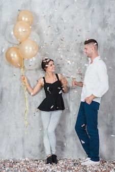 Coppia con palloncini e champagne