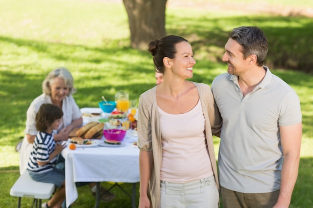Coppia con pranzo in famiglia al tavolo all'aperto