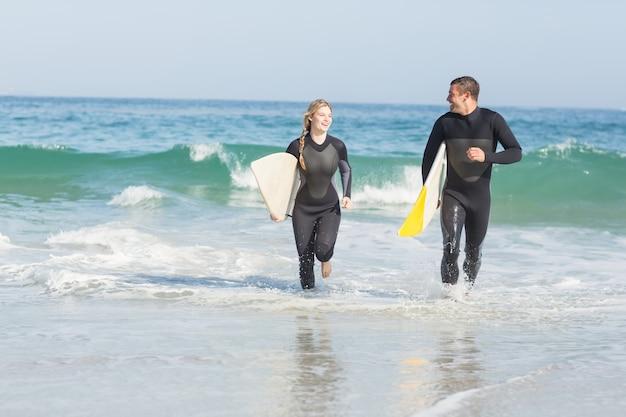 Coppia con tavola da surf in esecuzione sulla spiaggia