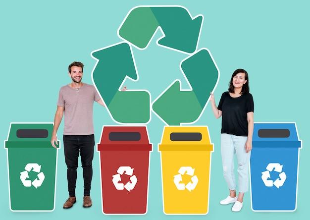 Coppia con un simbolo di riciclo e bidoni della spazzatura