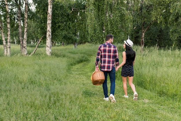 Coppia con una passeggiata in possesso di un cestino da picnic