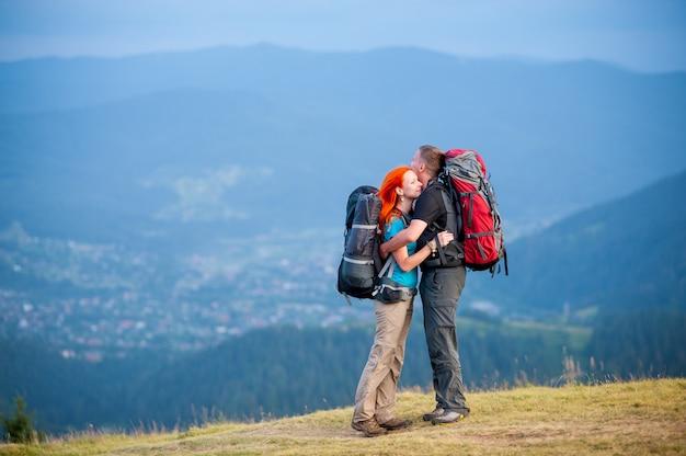 Coppia con zaini in piedi sulla strada in montagna