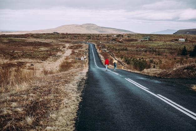 Coppia di adolescenti che si divertono pattinando e facendo discesa in islanda