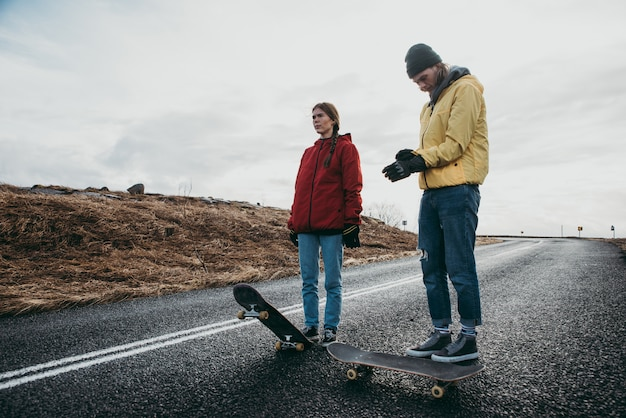 Coppia di adolescenti che si divertono pattinando e facendo discesa