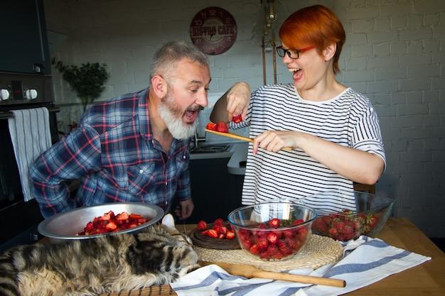 Coppia di adulti uomo e donna sbuccia e taglia le fragole per la marmellata di fragole