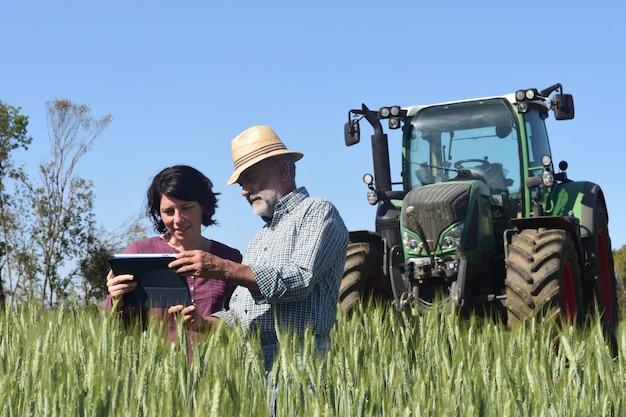 Coppia di agricoltori in un campo con una tavoletta digitale