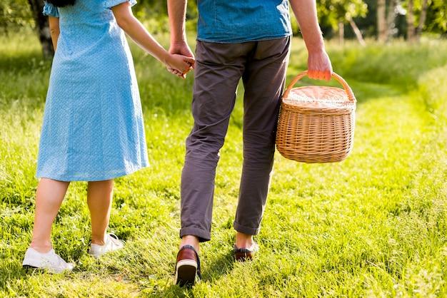 Coppia di amanti che passeggiano nel parco per mano