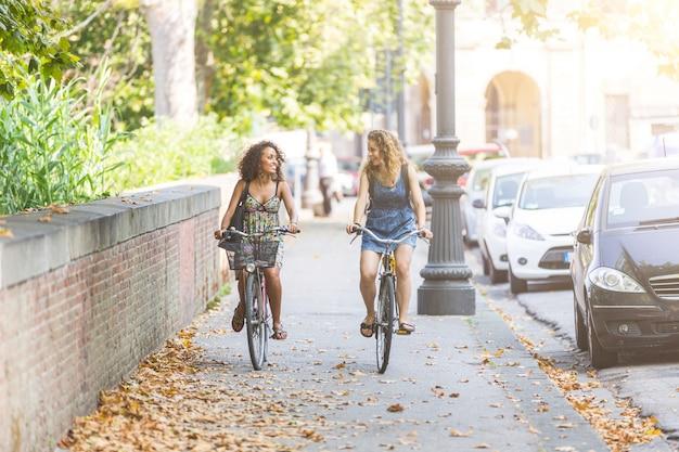 Coppia di amici con le biciclette sulla pista ciclabile.