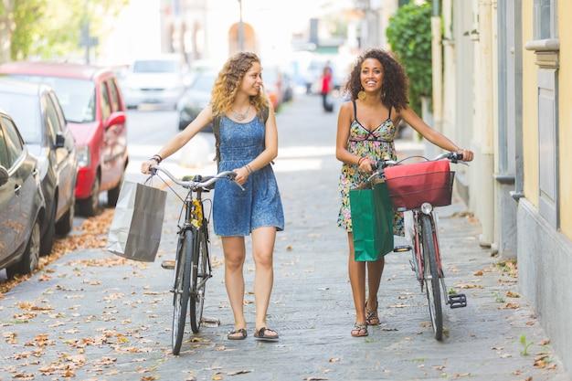 Coppia di amici multirazziale con bici.