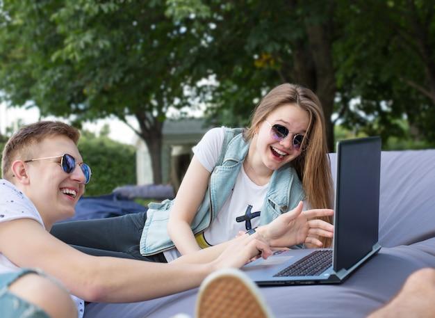 Coppia di amici rilassanti nel parco con il portatile.