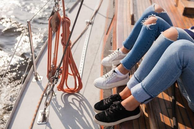 Coppia di amici sdraiati a bordo dello yacht durante una gita in barca