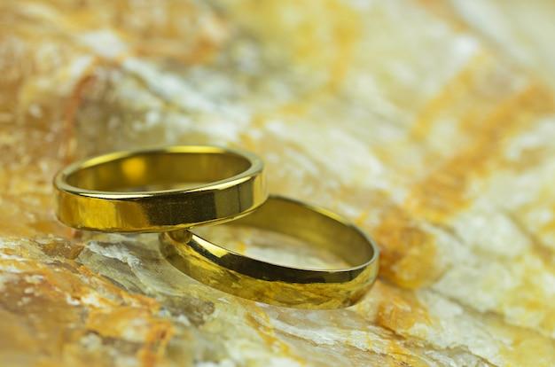Coppia di anelli d'oro su sfondo di pietra di marmo