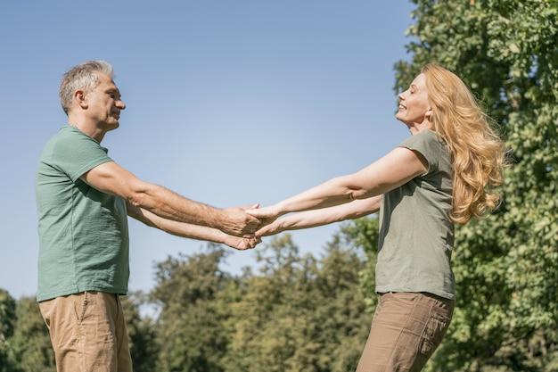 Coppia di anziani ballare nel parco