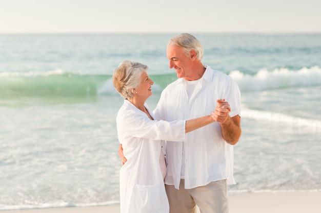 Coppia di anziani ballare sulla spiaggia